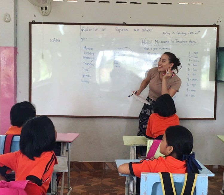 Volunteer teaching in front of a whiteboard
